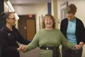 Michelle Brown, M.S.P.T., and a DMU D.P.T. student lead a patient through a balance exercise.