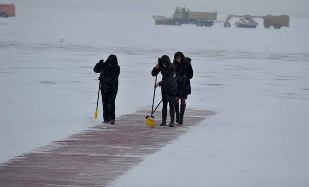 Червената пътека, по която трябваше да мине при слизането си от самолета държавният секретар на САЩ, беше често почиствана заради обилния снеговалеж.