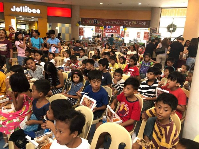 Children wait for the gift-giving at the fountain area of the Robinsons Mall.