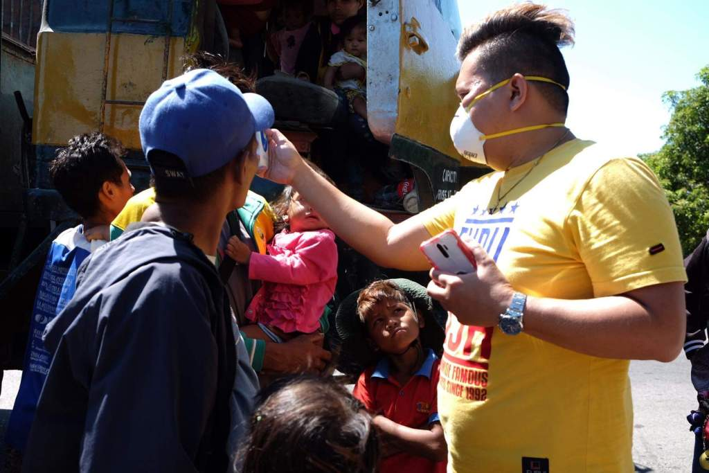 Bacolod battles COVID-19. Volunteer nurse Vicmar Ojoy checks temperatures of passengers -- migrant workers from Antique -- who were made to disembark from a truck at a southern checkpoint. | Photo by Banjo C. Hinolan
