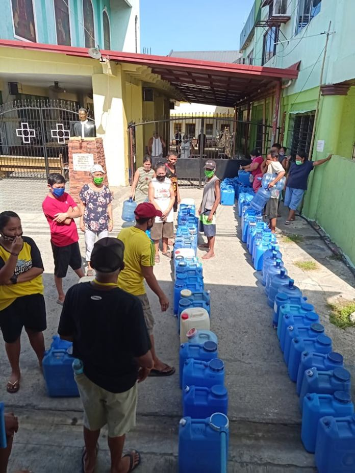 Residents of Brgy. Banago lining up their water containers