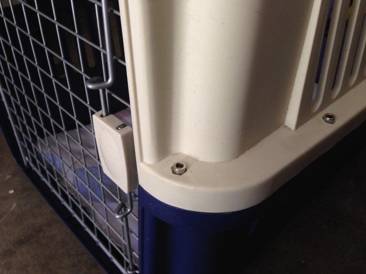 Secured dog travel crate with bolts