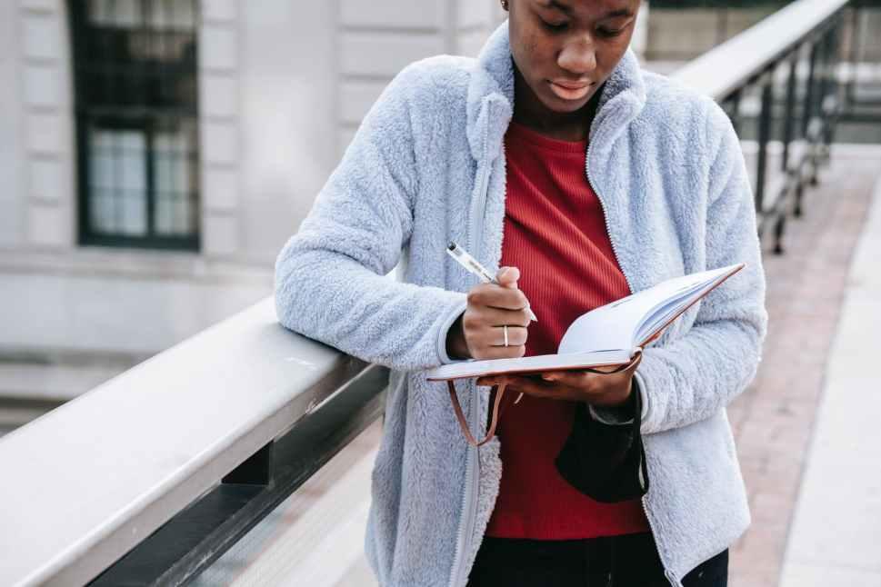 crop black woman watching agenda on city bridge