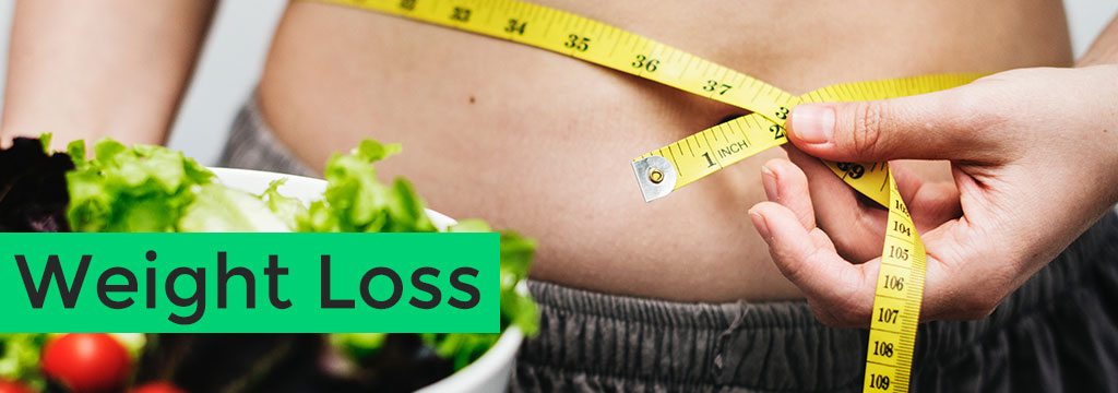 measuring person's stomach to see inches and weight loss