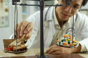 Man Weighing Pills in a Laboratory