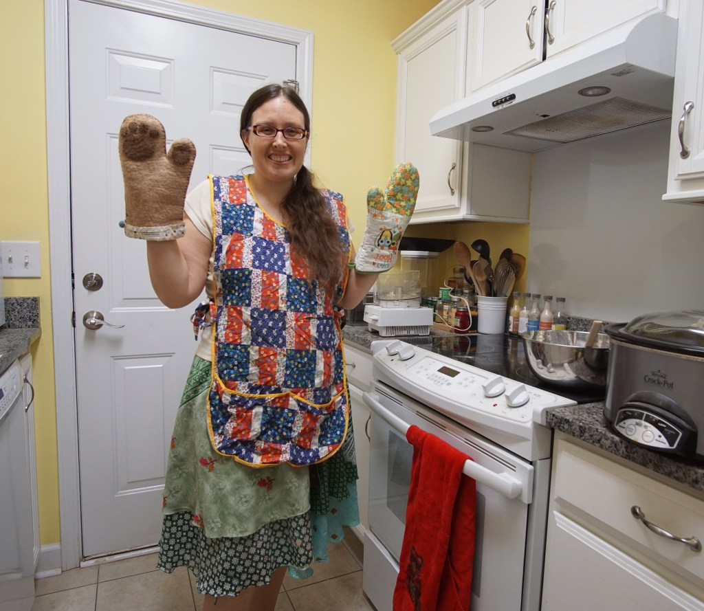 Veronica wearing a dog paw potholder, an owl potholder, and dressed in an apron her great-grandma made
