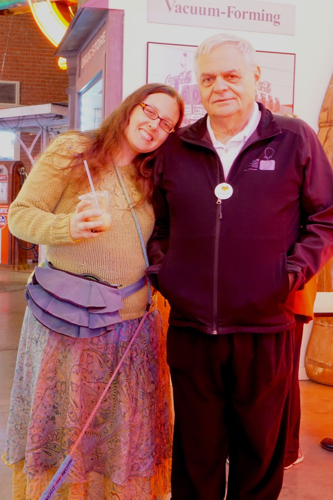 Veronica in her blue silk sari skirt and green cabled owls sweater holding an iced coffee and resting her head on her dad's shoulder.  He is wearing all black with a white shirt underneath his black jacket.