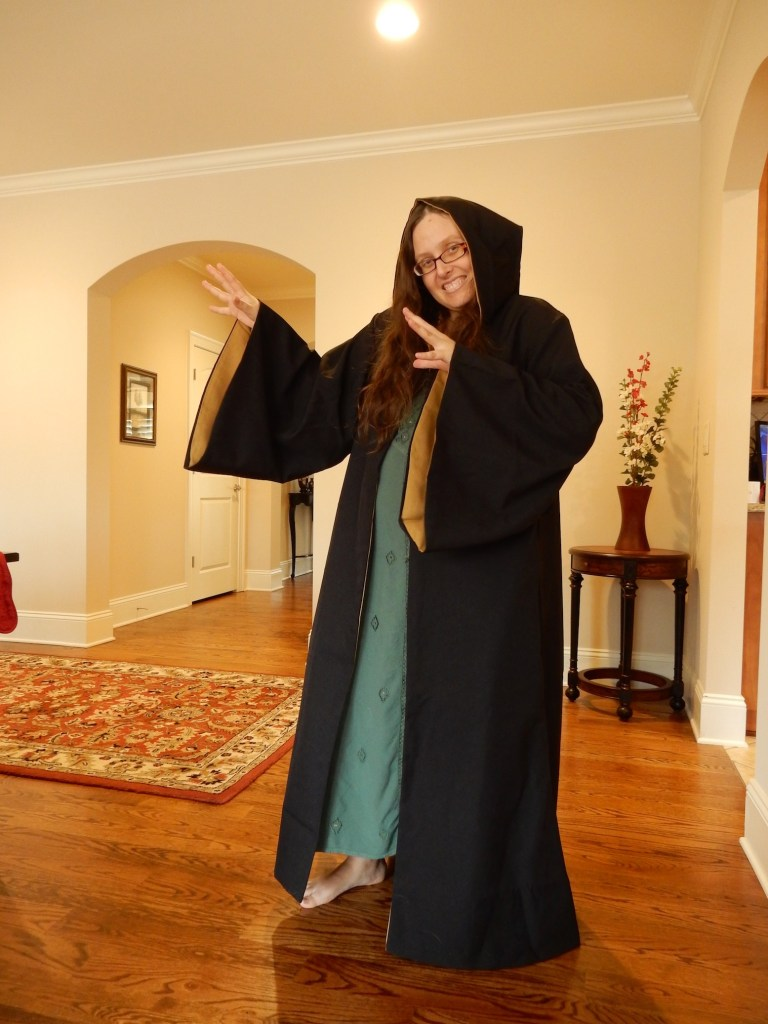 Veronica wearing a long black cloak from Hufflepuff house in Harry Potter!  Hufflepuff's colors are black and yellow, so the cape is black and the lining of the sleeves and hood is yellow.