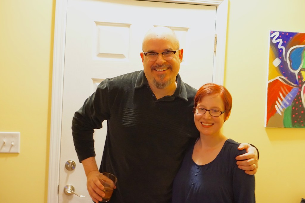 CJ and Melissa.  CJ is a tall bald man with a goatee, and Melissa is a more petite woman with awesome flaming dark red short hair.