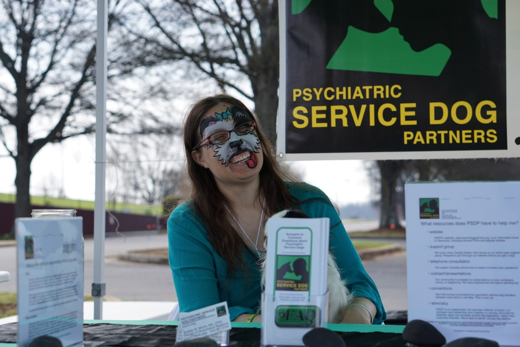 Veronica with her face painted tilting her head and laughing with a PSDP logo in the background.
