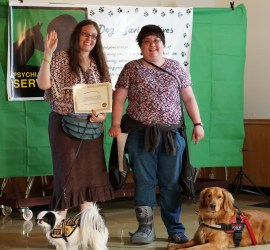 The pictures shows me, a woman with long curly brown hair, a brown skirt and a 70s shirt with a small black and white service dog wearing a Hufflepuff vest. The tester, Allison, is next to me. She is a shorter woman with short dark hair and a pretty floral shirt. Oh yeah, and she has a beautiful service dog who is a Golden Retriever.