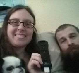 Bearded man holding Wii remote and long brown haired woman with glasses holding a small black and white dog.
