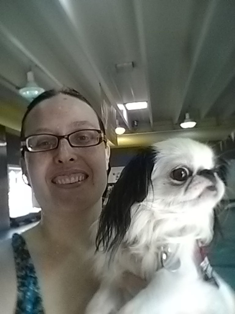 Selfie photo of Veronica in a blue swimsuit with wet hair, and a small black and white dog looking to the side.  The background is a pool.