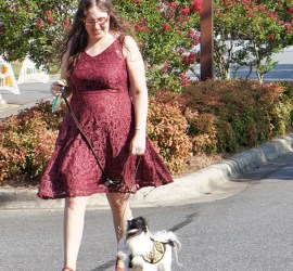 Veronica wearing a burgundy lace dress and red shoes, with long wavy brown hair, and Hestia wearing her yellow Hufflepuff vest, walking across the parking lot