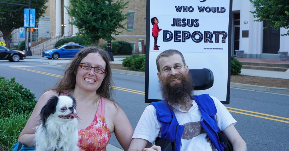 "Veronica and Brad. Brad is wearing his blue cooling vest. The front of his sign reads ""WWJD, who would Jesus deport?"""