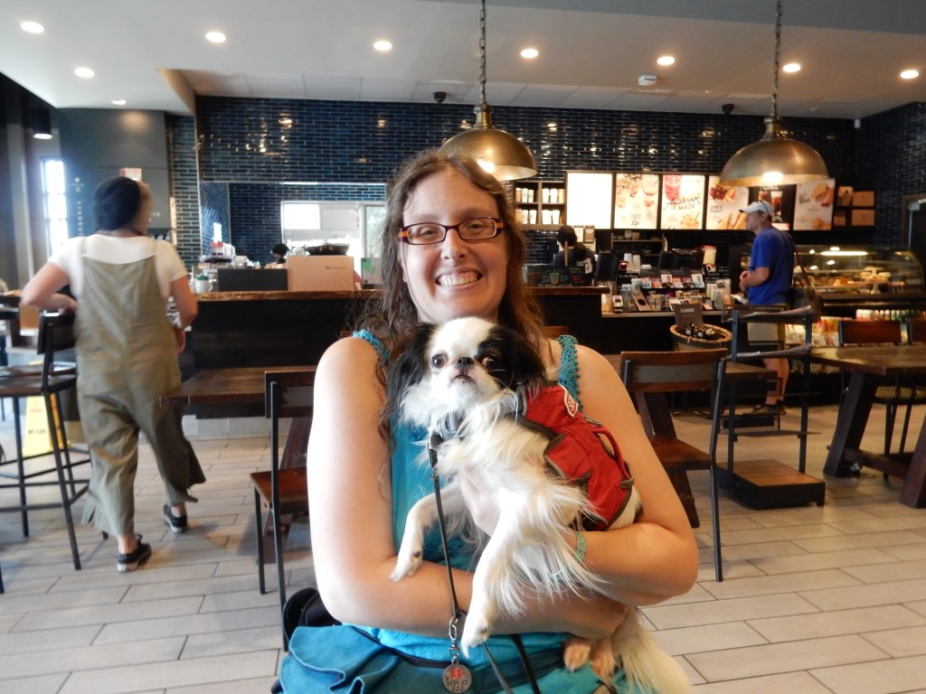 Hestia and me.  I am a 30-something woman wearing a turquoise dress with long brown hair.  Hestia is a small black and white dog wearing a red ruffwear webmaster harness.