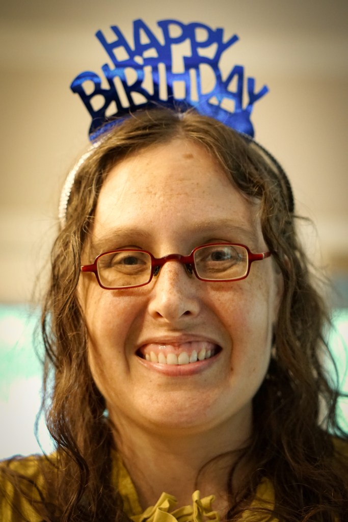 Closeup of Veronica's face with her red square glasses and a happy birthday tiara on her head.