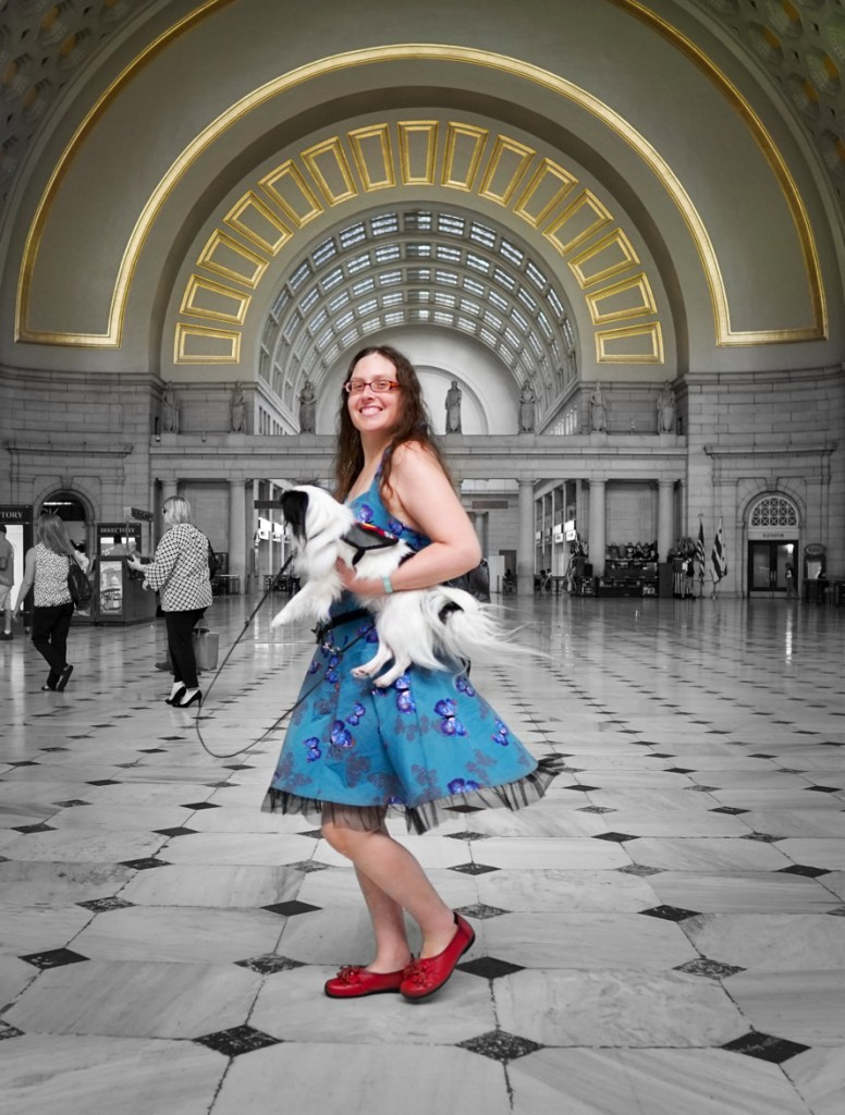 Veronica holding Hestia mid-twirl in the Union Station lobby. Veronica, Hestia, and the gold parts of the wall are in color. The rest of the pic is black and white.