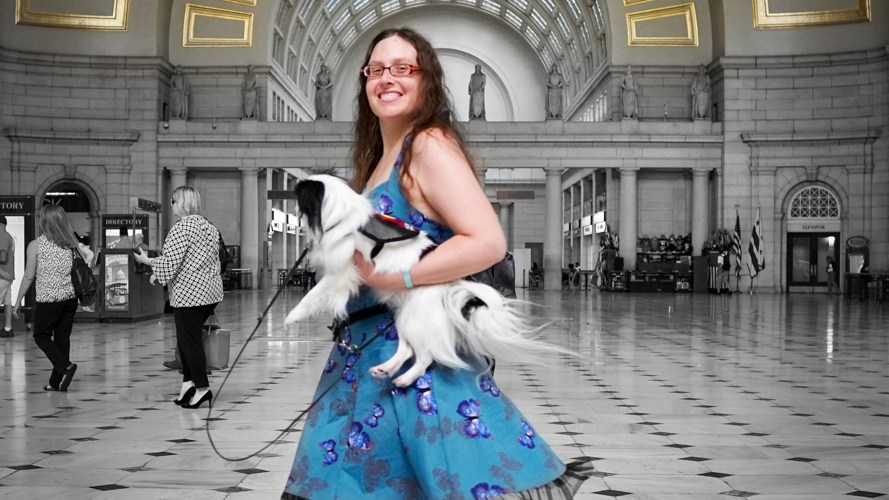Veronica in blue butterfly dress with red shoes, twirling in the middle of Union Station. Veronica and Hestia and the golden ceiling are in color, the rest is black and white.