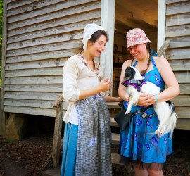 The interpreter, dressed in a white linen top and a blue skirt and blue apron, interacts with Hestia a little before getting a picture with Veronica.
