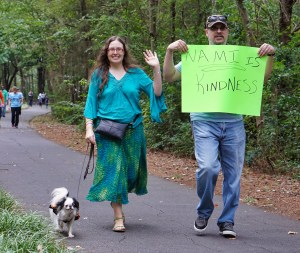 """Hestia wearing an orange and black dress, Veronica wearing a turquoise outfit and waving to the camera, and CJ wearing jeans and holding a sign that reads """"NAMI is kindness"""". This was take during the walk!"""