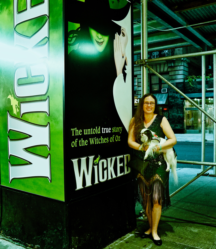 Veronica in a green art deco dress and Hestia in a green vest. They are posing next to the Wicked sign before watching the show!