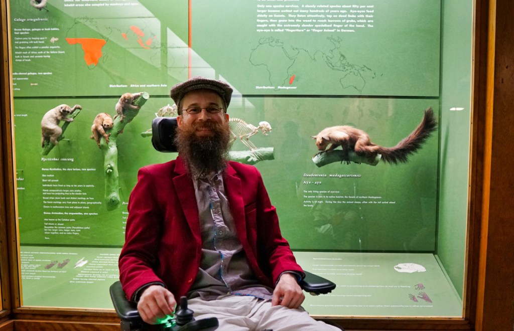 Brad wearing his red blazer and his driving cap (that he knitted!) in front of the Tarsier in the museum.