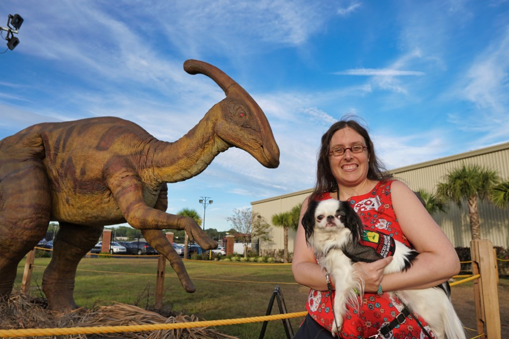 Veronica holding Hestia in front of another dinosaur who is rearing up on its back legs.