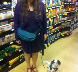 An old photo of Veronica and Hestia in Earth Fare. Veronica is wearing a purple long sleeved dress, and Hestia is in her turquoise Omni-Vest. They are standing in front of a food display and smiling at the camera.