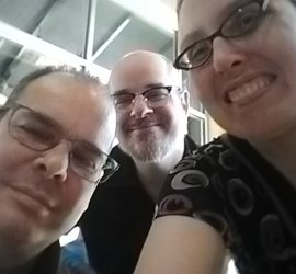 Selfie of Dan, CJ, and Veronica. All three have glasses. CJ and Dan have short hair. CJ also has a beard. My long hair is tied up in a ponytail from swimming!
