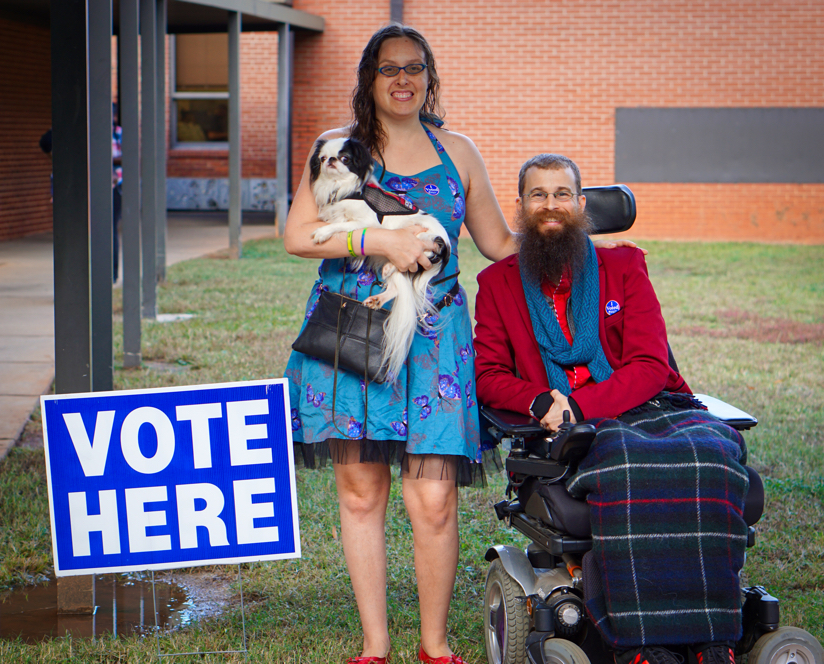 """Brad in his red blazer and plaid blanket next to Veronica wearing her blue butterfly vest and holding Hestia in a red mesh vest next to a """"vote here"""" sign."""