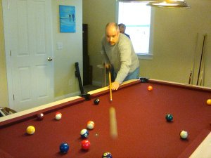 Action shot of CJ shooting pool. Man in a grey shirt with salt and pepper hair and beard. You can see the white ball in motion.