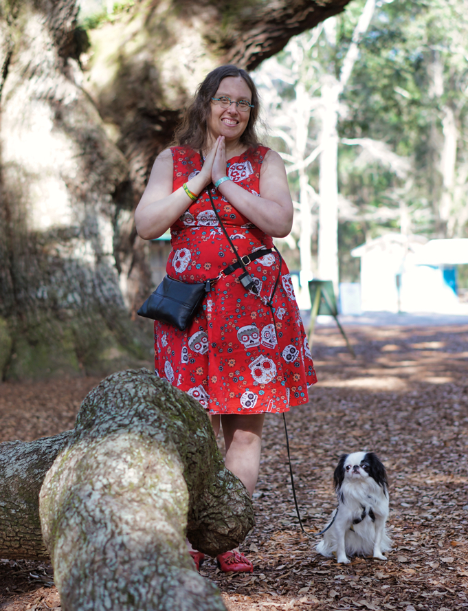 A 38 year old woman with long curly brown hair wearing a red dress and shoes (Veronica) poses next to the Angel Oak tree with Hestia sitting on the ground next to her.