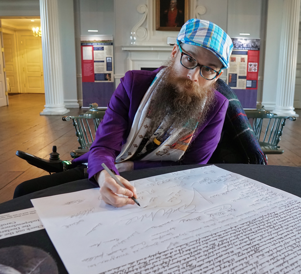 Brad signing the Declaration of Independence.  He is wearing a purple blazer and a blue plaid hat, and gives the camera a very serious look.
