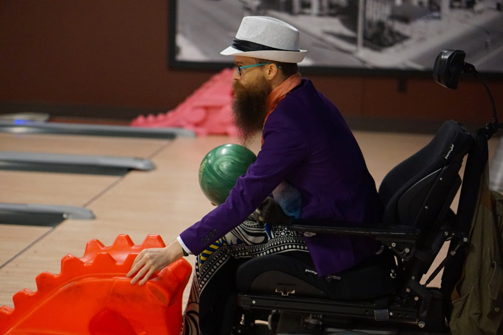 Brad is wearing a purple blazer with an orange scarf, and a white hat.  He holds a green bowling ball and prepares to use the red plastic dinosaur kids bowling implement to launch his ball down the lane.