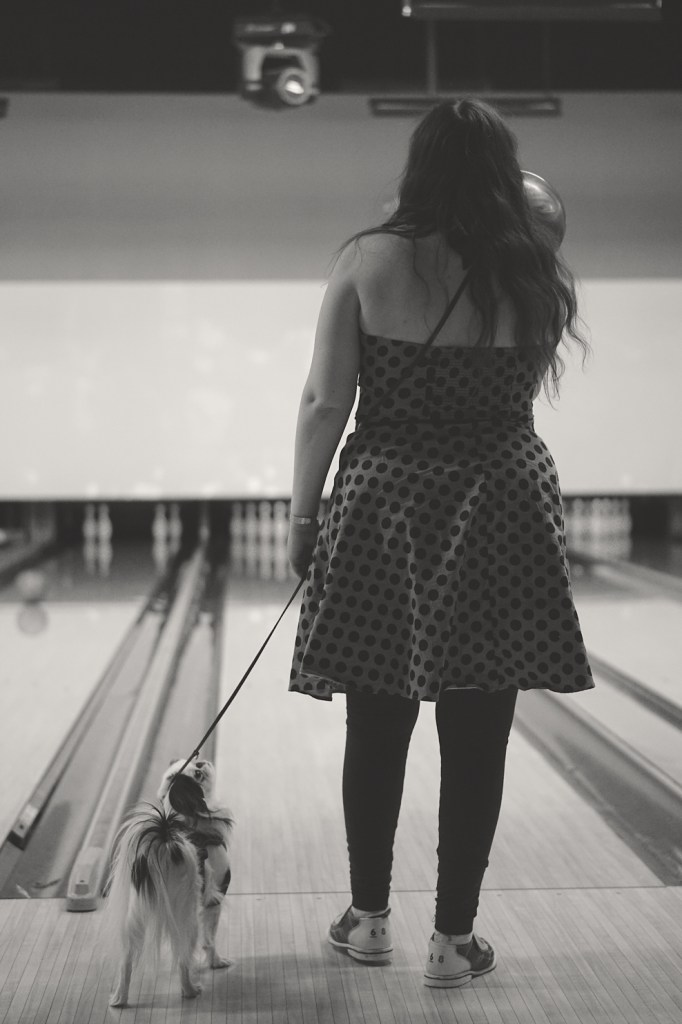 Black and white photo of Veronica holding up her ball getting ready to throw it, with Hestia looking up at her.