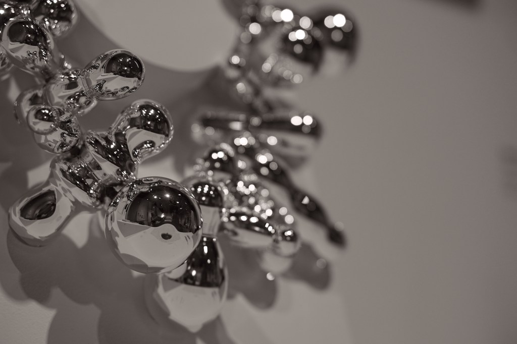 A closeup of some of the jewelry in the museum.  It is shiny silver balls, and if you look closely you can see Veronica and Brad's reflections.
