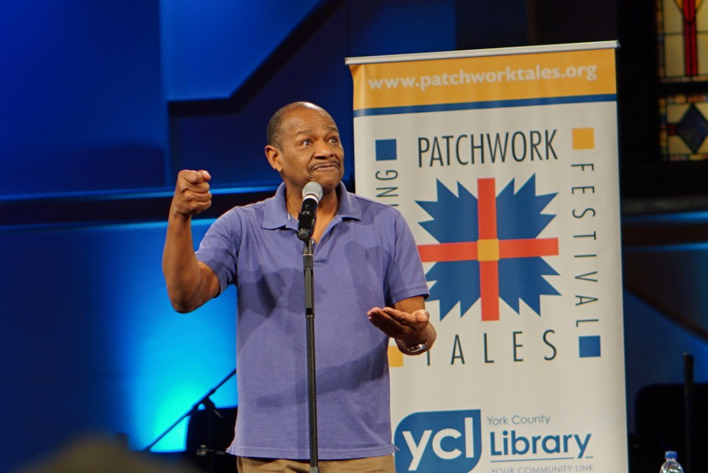 The second storyteller is a black man wearing a denim-blue polo shirt.  He gestures with his hands and is making some sort of sound effect with his mouth.