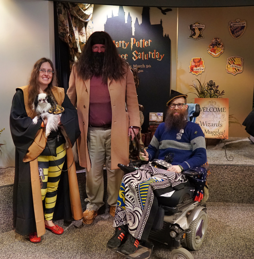 Veronica, Hestia, and Brad smiling with Hagrid, with Brad's wand at the ready