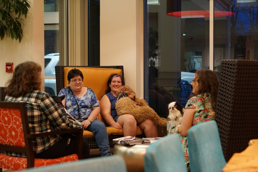 Deanna with Max, Allison, Hannah with Sasha, and Veronica with Hestia sit around a coffee table in the hotel lobby