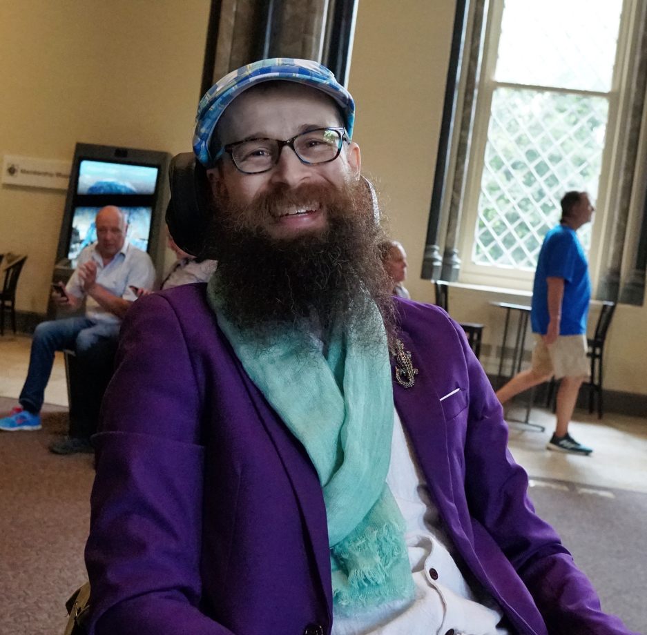 Brad wearing a white linen shirt, a purple blazer, a crocodile broach, a turquoise scarf, and a blue plaid driving cap.  He is smiling at the camera while in the Smithsonian Castle.