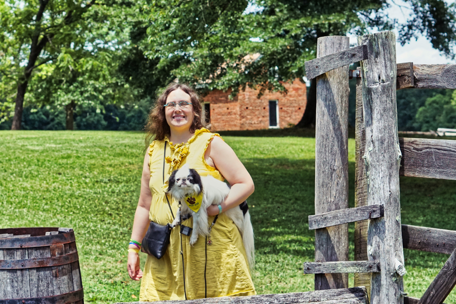 Veronica is carrying Hestia, and they pose next to a fence with one of the slave cabins in the background.