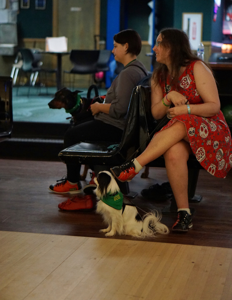 Veronica, wearing a red skull dress in the bowling alley, looks over her shoulder.  Hestia sits on the floor looking in the same direction.  Sitting on the other side of the seats is Nicole, a woman with brown hair and a grey shirt. Her Doberman Link stands next to her.
