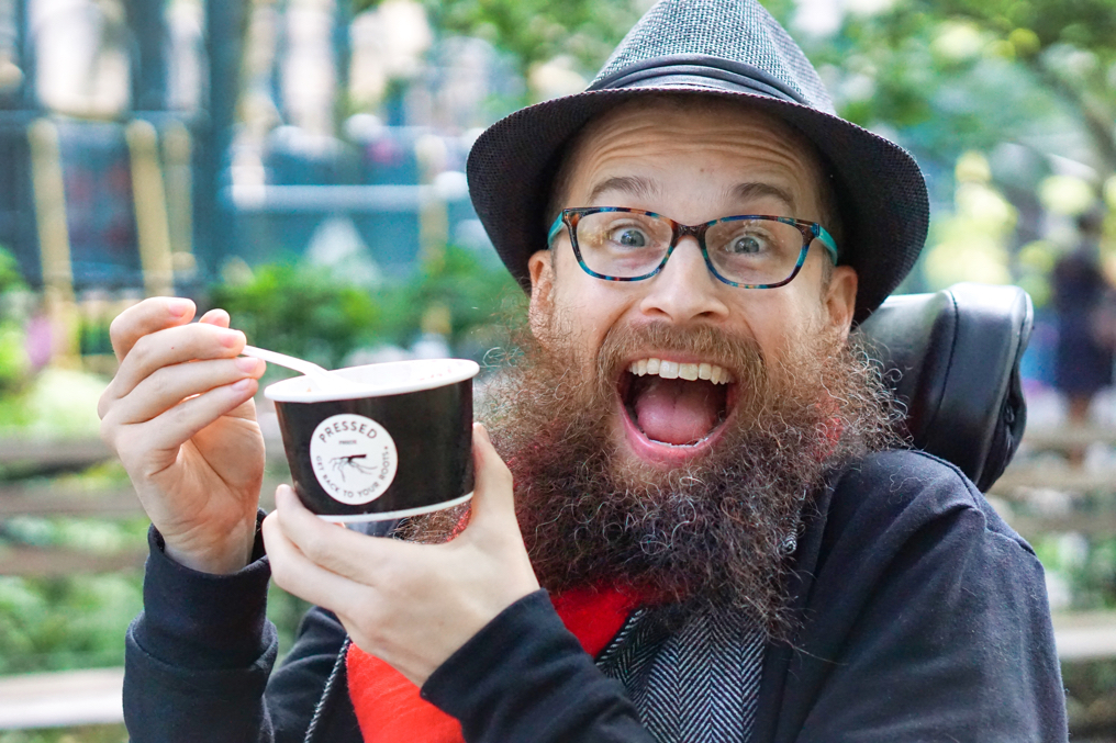 Brad holds up his Pressed Juicery freeze and looks so excited about it that he might burst!