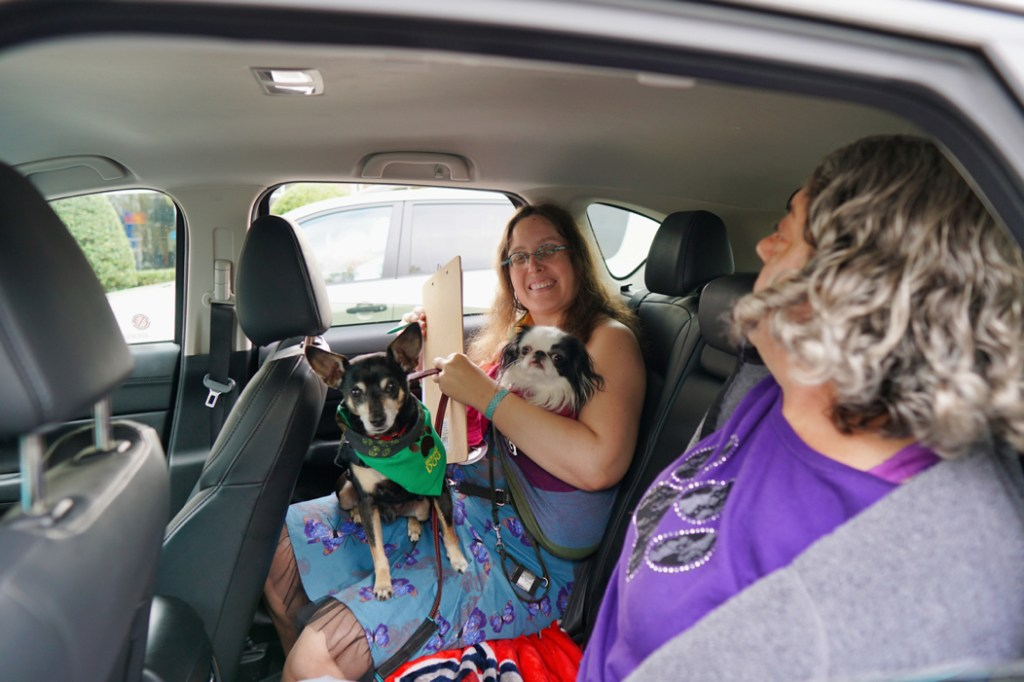 Veronica sits in the backseat of Deanna's car, holding Hestia and Max.  Next to Veronica sits Kyrie, a woman with curly grey hair and a purple shirt.
