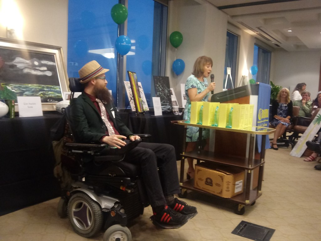 Brad sits in his power chair at the front of the room, looking at Betsey who is talking at the podium.  Betsey is introducing Brad for his award!