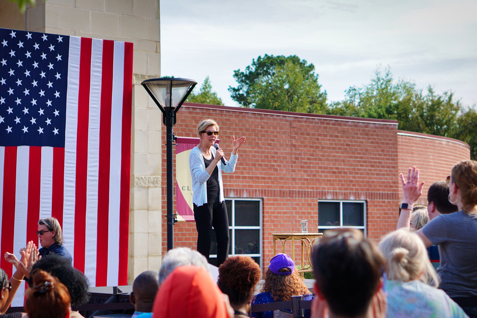 A clearer shot of Warren up on stage lifting her left hand and gesturing.