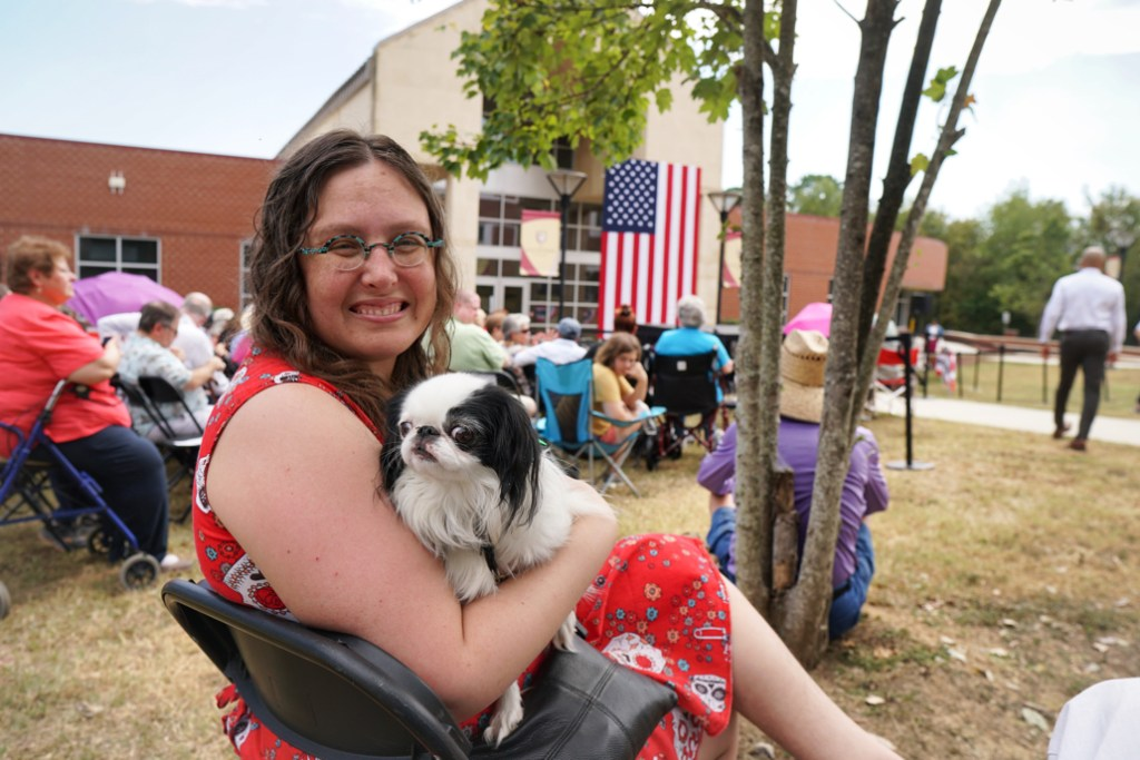 This picture was taken when we first arrived, and the ADA section had yet to fill up.  I am looking over my shoulder with Hestia on my lap.  In the background is a stage with an American flag backdrop.