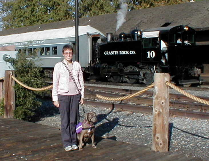 Veronica and Sabrina pose in front of a steam engine.