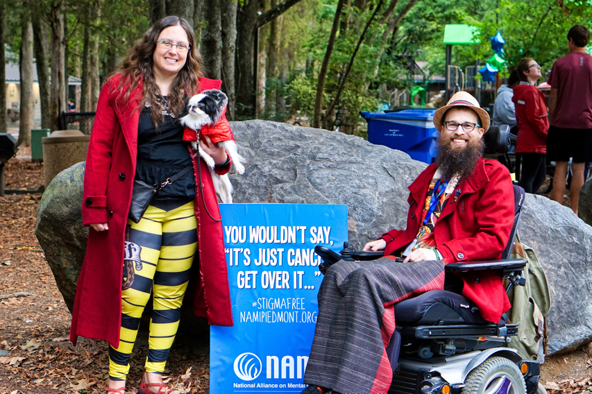 """Veronica with Hestia on the left of a sign, and Brad on the right of the sign.  The sign is propped up against a large rock and reads """"You wouldn't say, 'It's just cancer, get over it...'"""""""